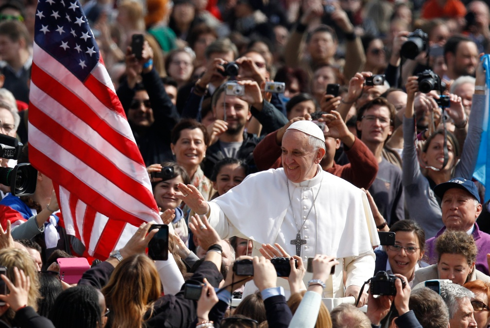 The U.S. flag is seen as Pope Francis greets the crowd during his arrival to lead his general audience in St. Peter's Square at the Vatican March 27. (CNS photo/Paul Haring) (March 27, 2013) See POPE-AUDIENCE March 27, 2013.